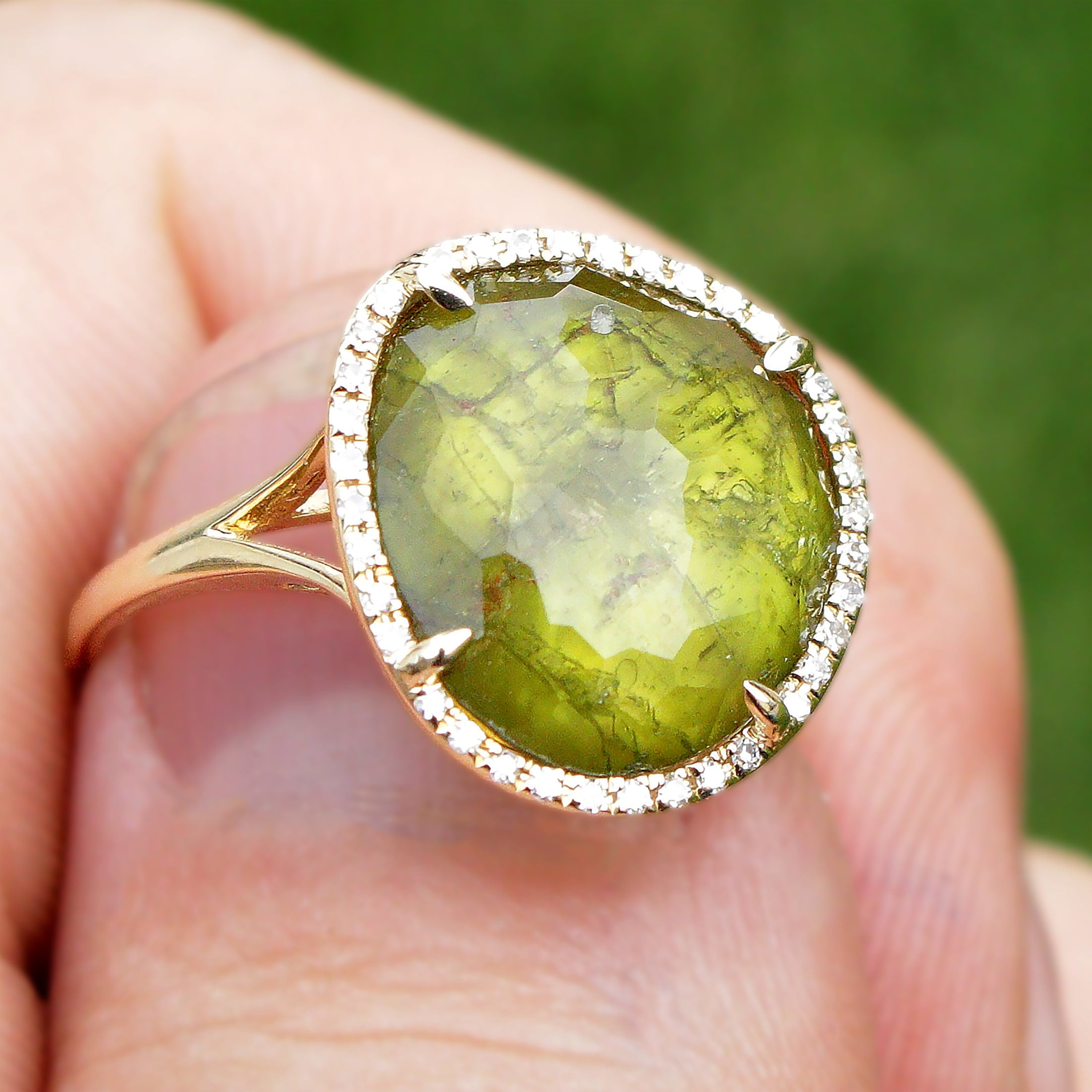 Green tourmaline ring with halo and inclusions.