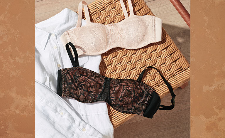 Two lacy strapless Amourette Bras laying on bench