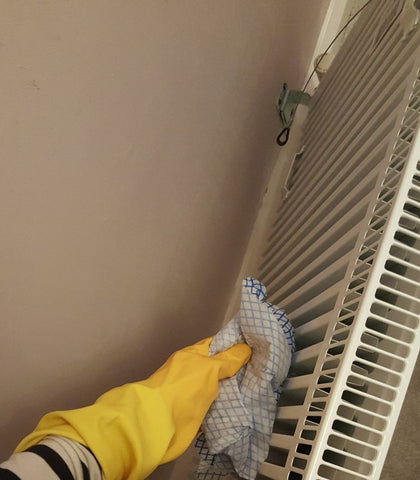 cleaning behind a radiator