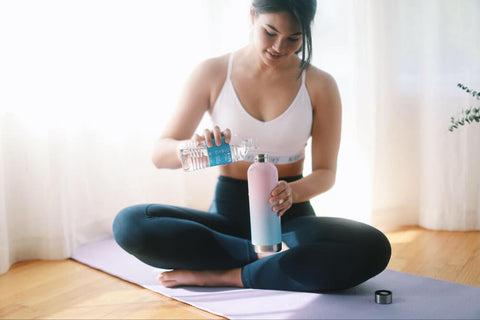 woman adding E-Lyte from BodyBio to her water