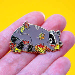 Sleeping raccoon in fall leaves enamel pin
