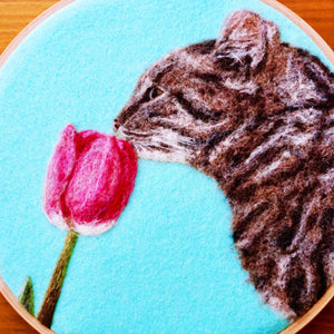 Wool painting of a cat smelling a tulip