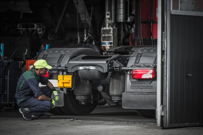 Service technician inspecting the Volvo truck parts at the back of the truck's cab