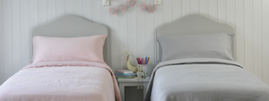 Two Childrens Beds with Natural Linen Bedding in Pink and Grey