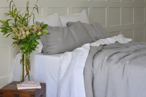 Untidy Bed with Grey and White Linen Sheets UK