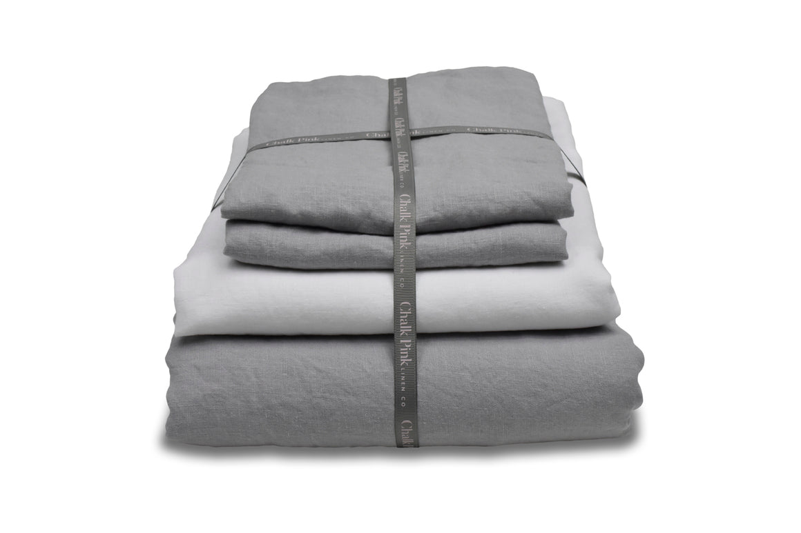 Grey Linen Bedding with a White Sheet in a Bundle