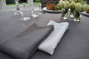 White Linen Folded Napkin on top of a Dark Grey Linen Tablecloth