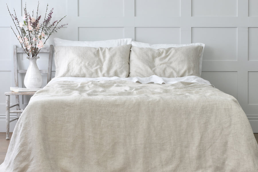 Natural Flax Linen Bedding on a Bed in a Bedroom with a Grey Pannelled Wall