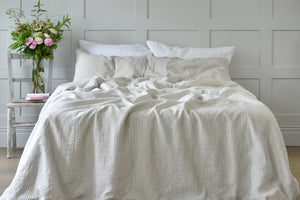 A Bed with Ticking Stripe Bedding on in a Bedroom