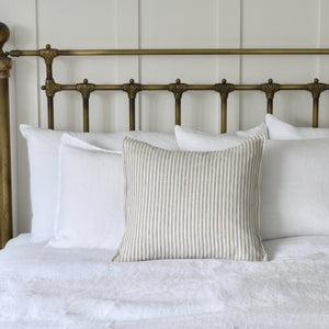 Grey Ticking Stripe Linen Cushion on a White Linen Bed