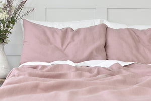 Vintage Rose Pink Linen Pillow on a Bed with White Linen Sheets