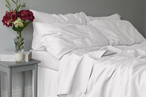 Light Grey Linen Duvet Set with Matching Linen Sheets in a Bedroom