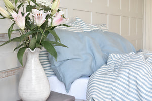 Blue Ticking Bedding on a bed with Light Blue Linen Pillowcases