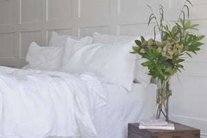 White Pure Natural Linen Bedding on a King Bed with Flowers on a Table