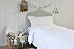 Neatly made White French Linen Bed with Grey Headboard