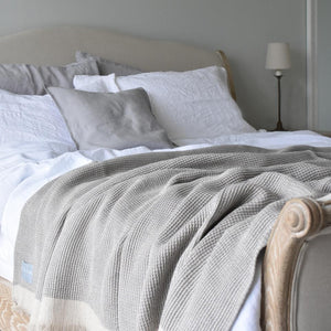 Grey Linen Throw on a Bed with White Linen Duvet Cover and Cushions