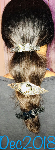 Woman with hair that has grown rapidly. Hair is in one ponytail with many hair clips.