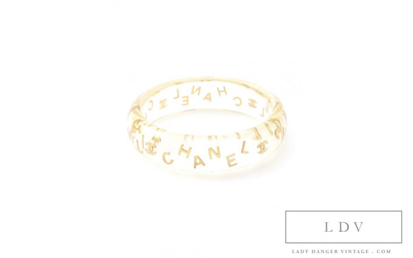 Vintage CHANEL Clear Lucite Bangle featuring gold tone floating letters and Chanel logo