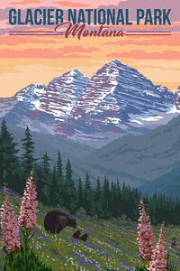 Idyllic scene in Glacier National Park Montana of a mother bear and her cubs amongst the Spring bloom and mountains