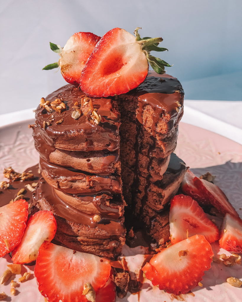 Stack of chocolate pancakes with choc sauce and fresh strawberries