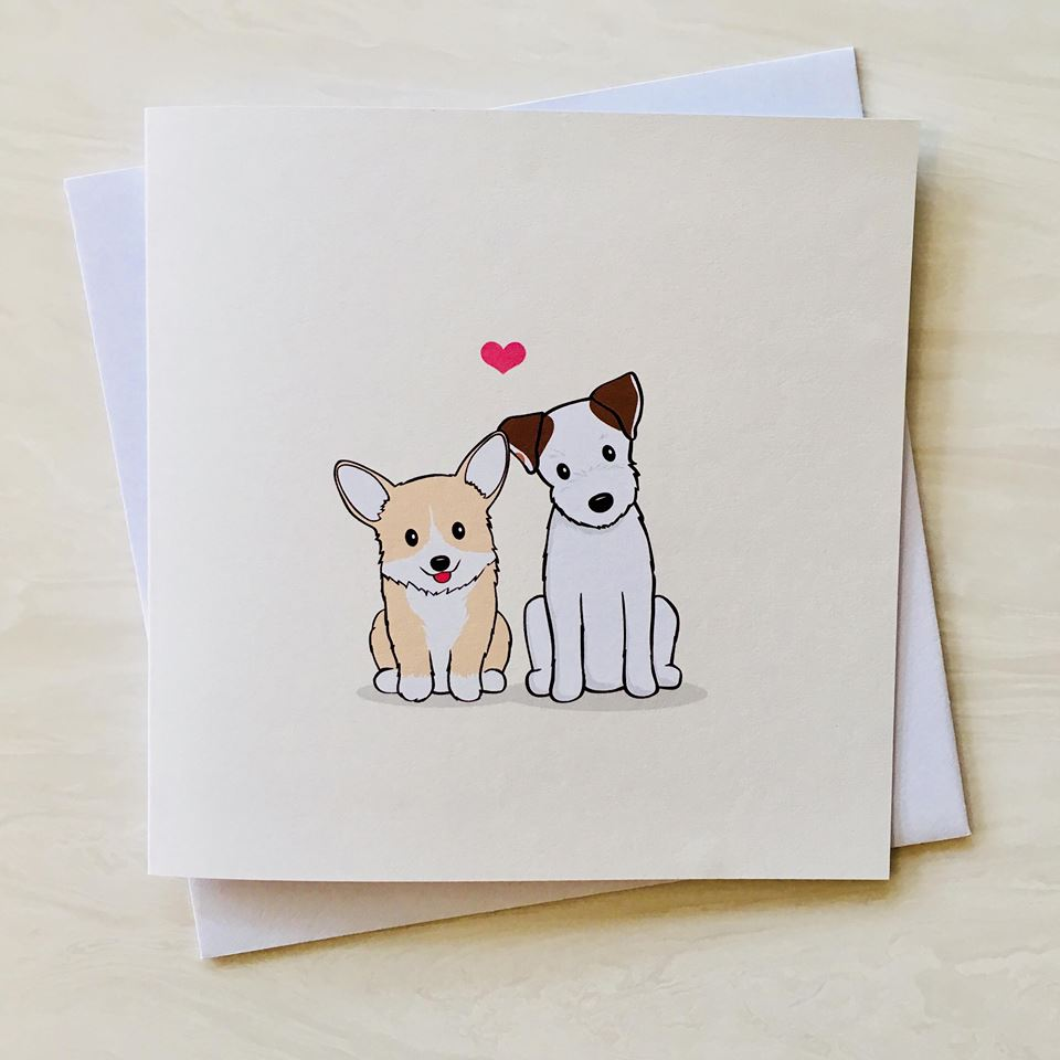 greeting card with cartoon jack russell and corgi dogs sitting together with a love heart above their head