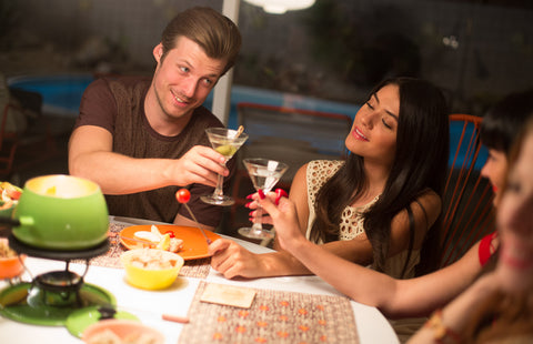 Mr. California in Midcentury Modern Lifestyle scene with attractive girl making a toast at fondue.