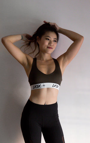sport woman with abs wearing LXIX dri fit forest green sports bra and leggings in singapore