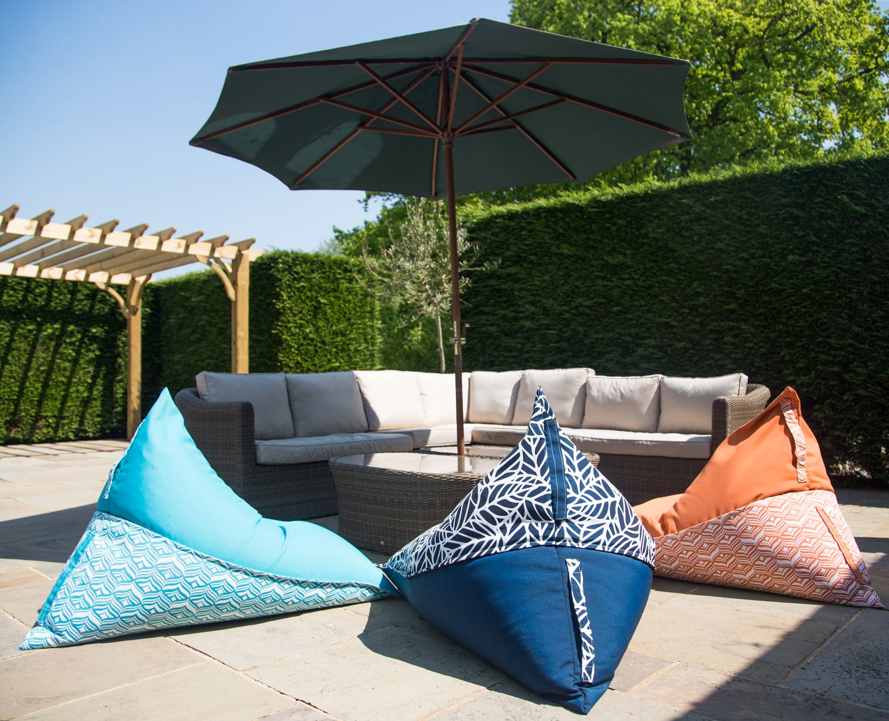 Outdoor bean bag chairs in ocean, navy and orange ready for lounging on in the sunshine