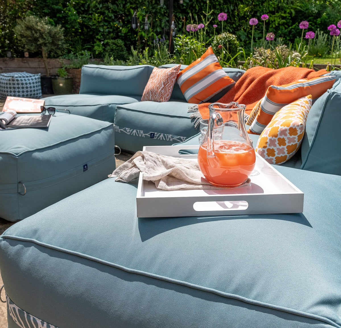 Garden sofa and ottoman in ocean blue, with bright orange weatherproof cushions