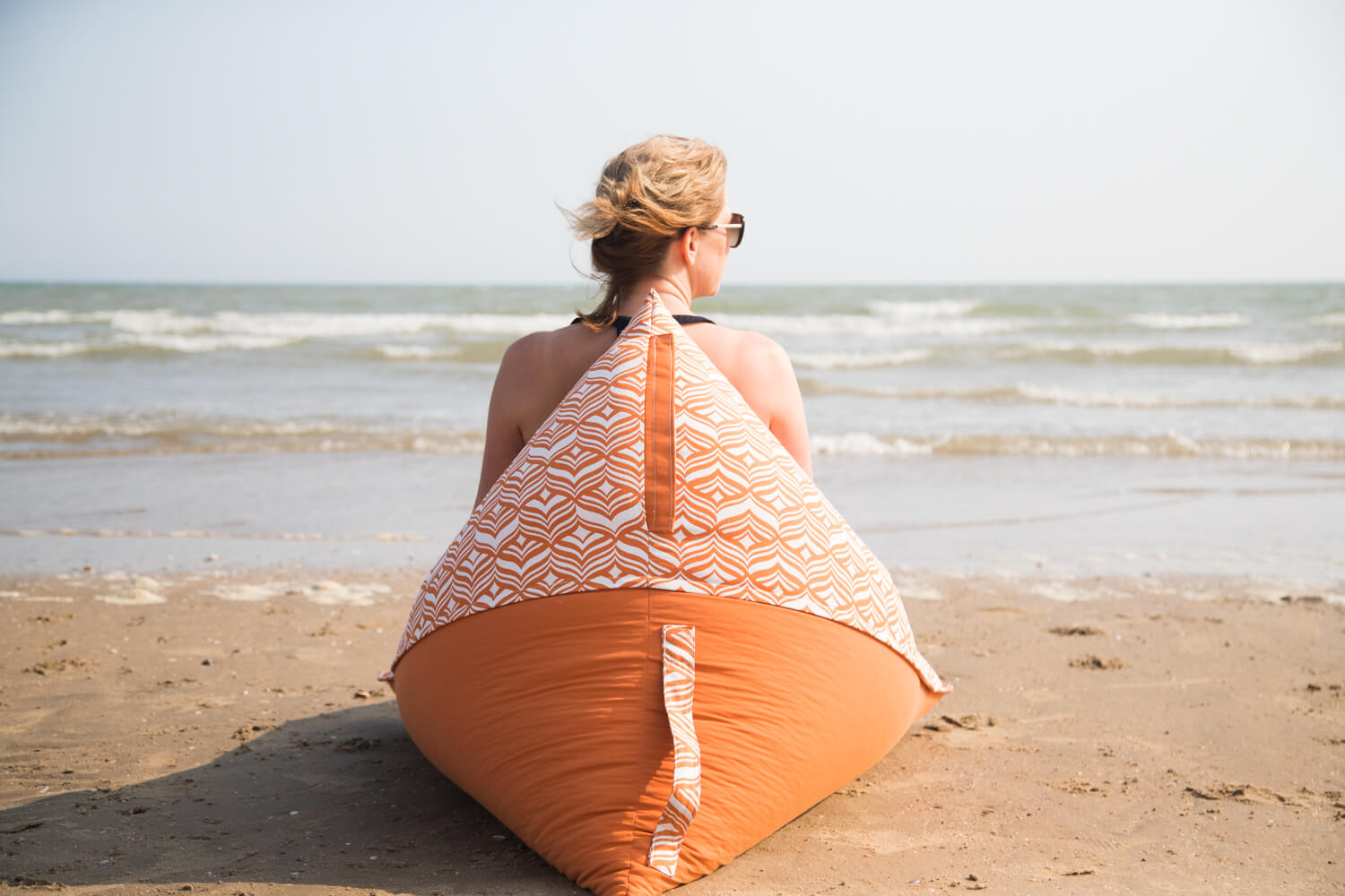 A woman sits on an orange beach lounger beanbag looking out at the waves
