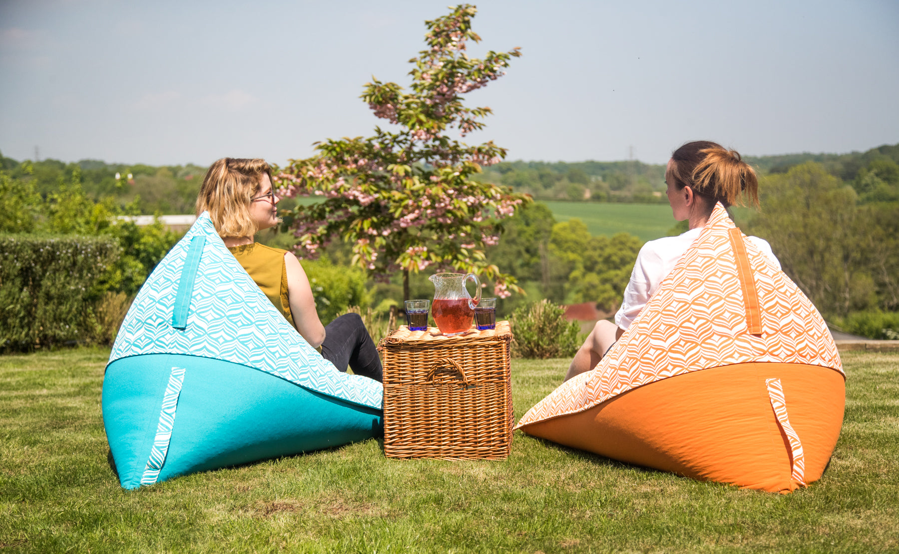 Two friends chat amiably from the comfort of garden bean bag chairs