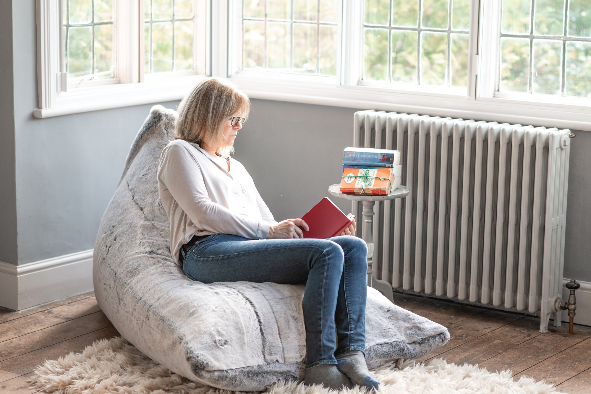A snuggly faux fur bean bag in Alaska Fox is the cosiest reading corner for the woman snuggled into it with her pile of books