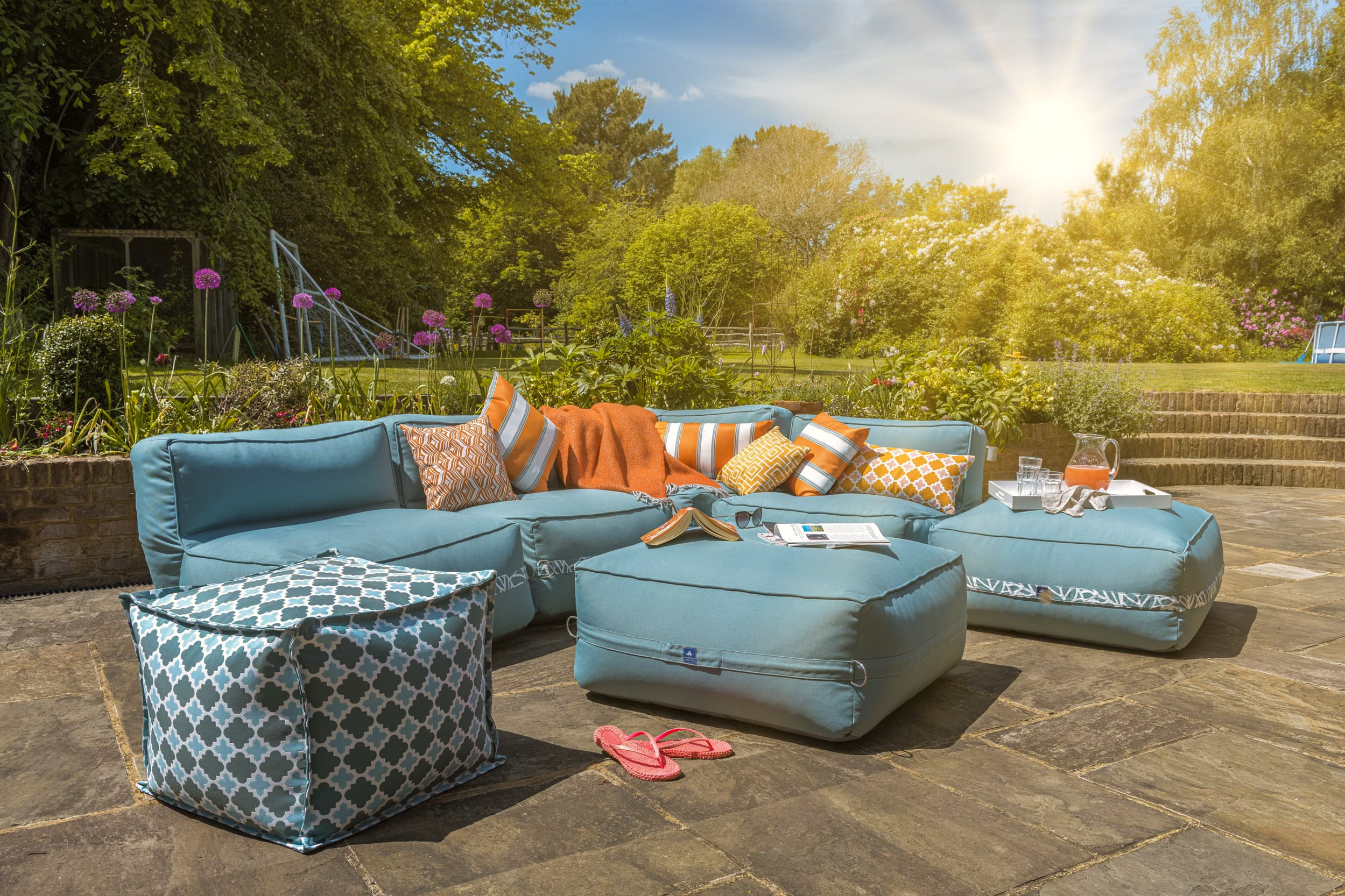 A garden sofa in ocean blue at a sunny BBQ party
