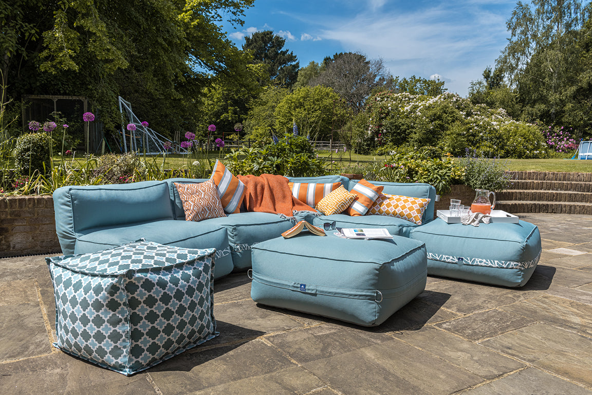 Garden sofa and ottoman on a perfectly positioned patio to catch the sun