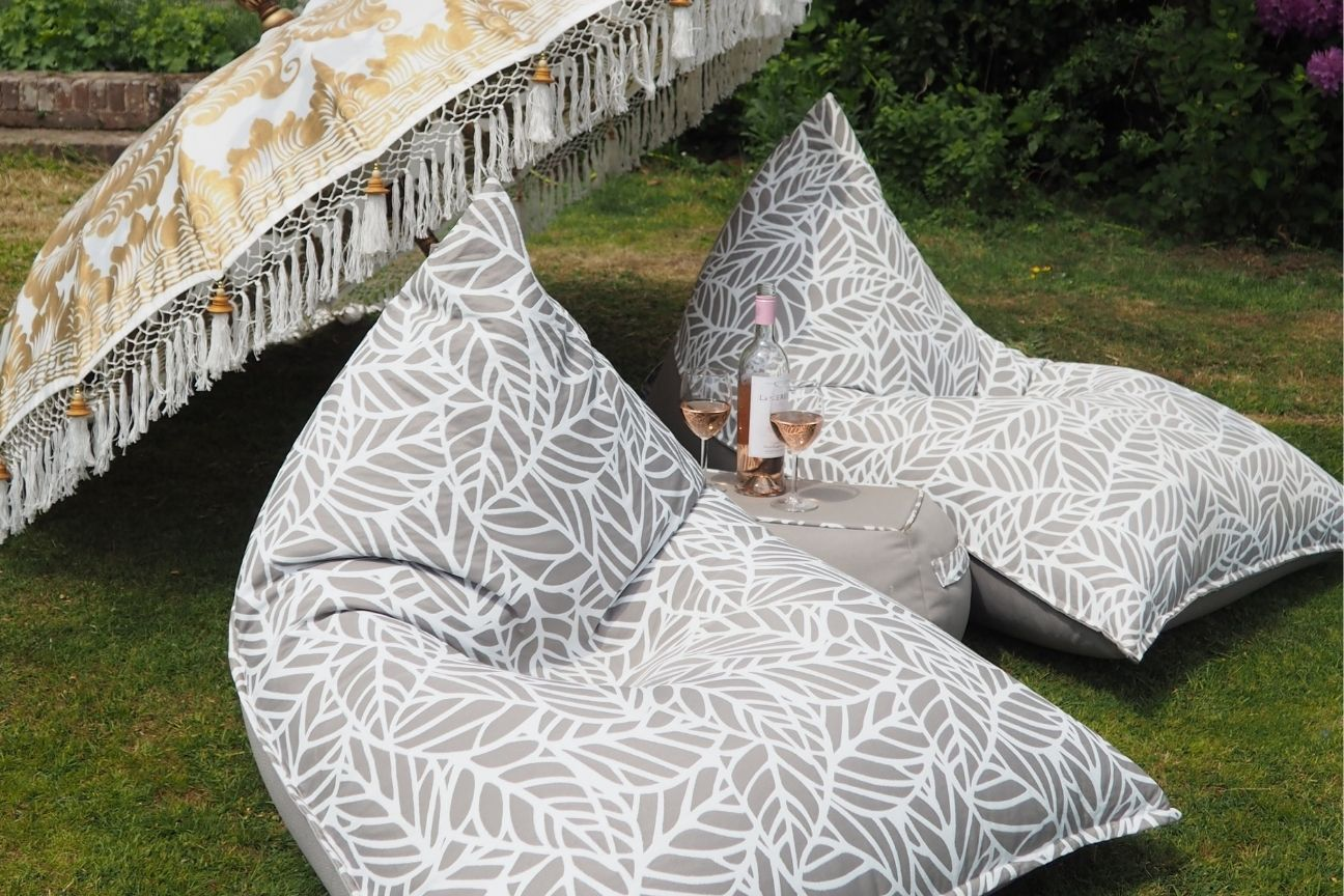Two luxury outdoor loungers sit on the grass under a parasol