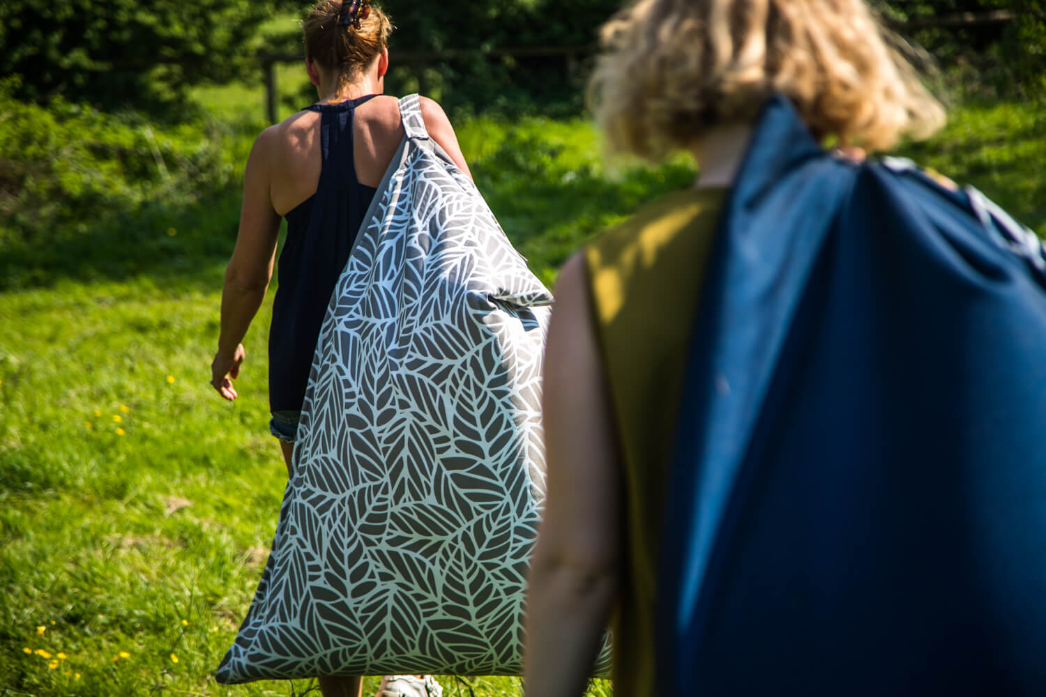 Two women easily carry their beach chair bean bags using the carry handle sewn on the back
