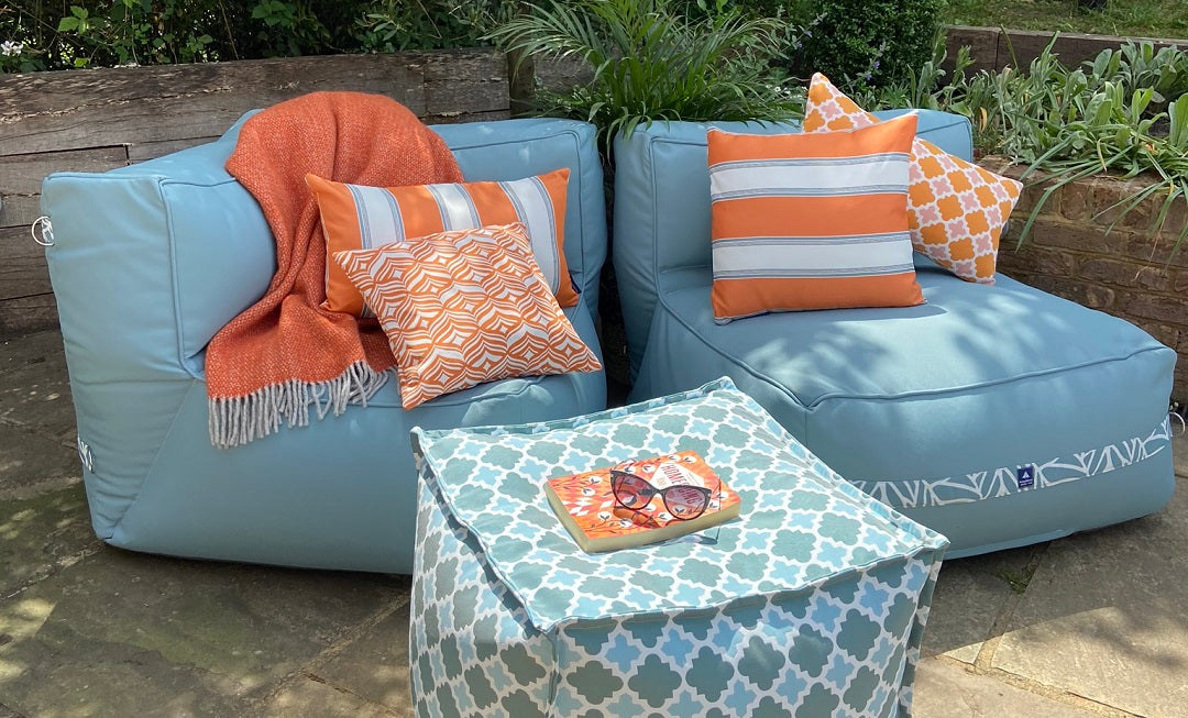 Garden sofa chairs and an outdoor pouffe decorated with orange cushions