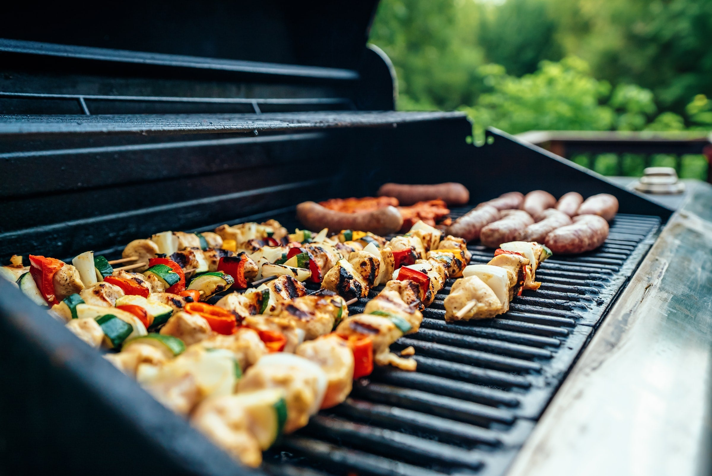 Chicken kebabs and sausages sizzling on a BBQ grill