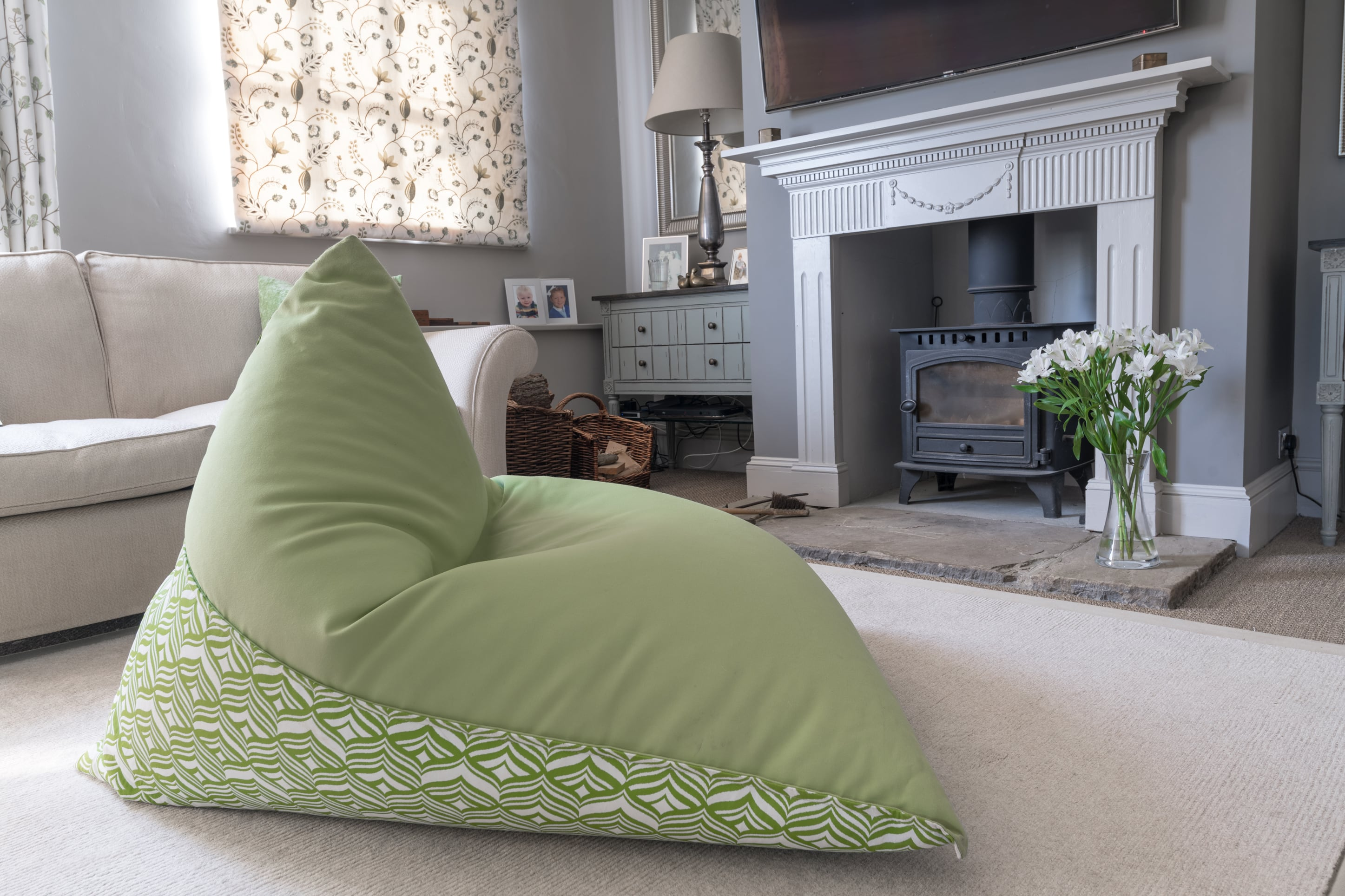 Armadillo Sun bean bag chair in green and white tulip design indoors by fireplace