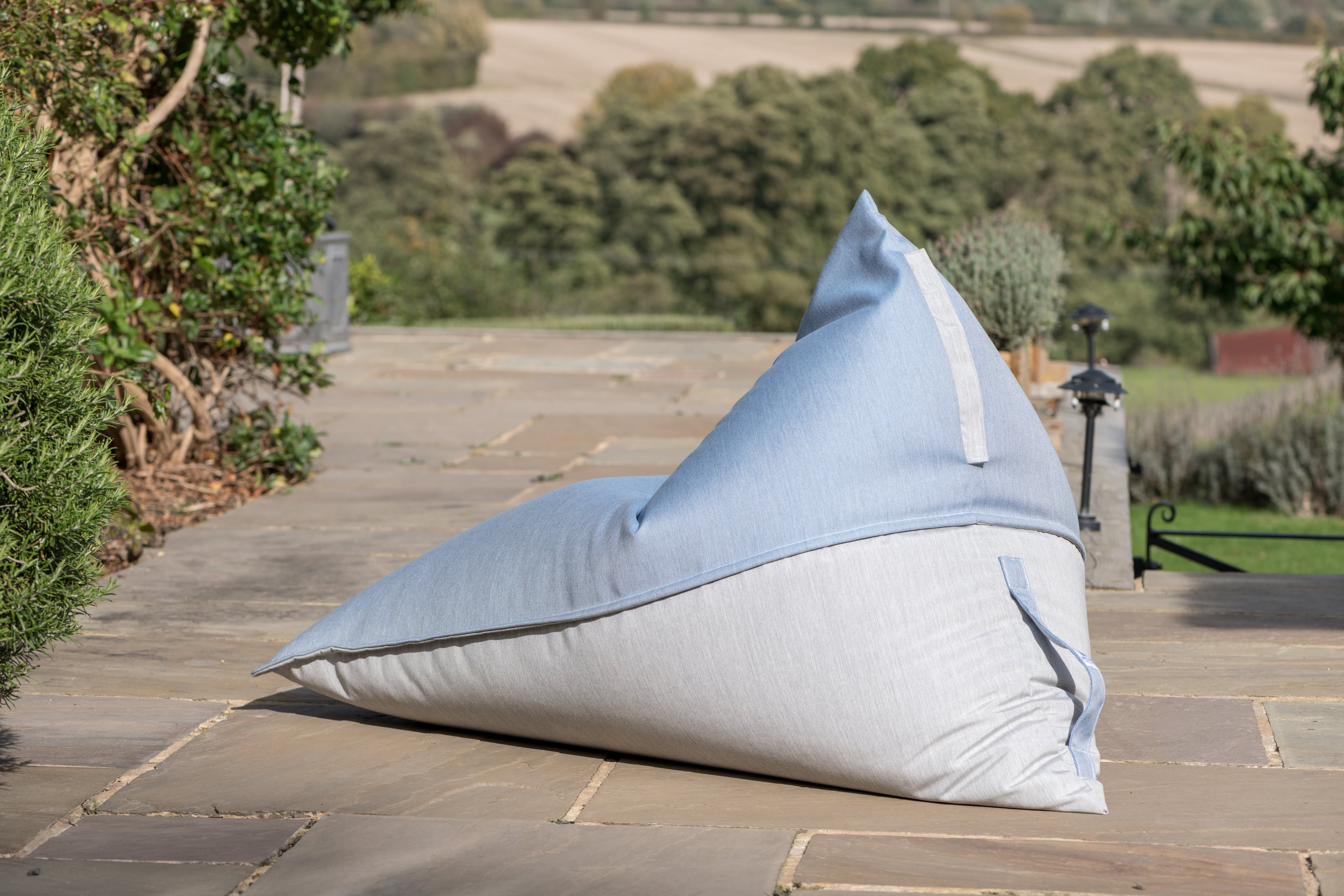 Armadillo Sun bean bag lounger in cool blue and grey fabric outside