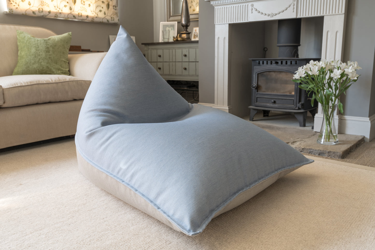 Armadillo Sun bean bag lounger in cool blue and grey fabric inside by fireplace