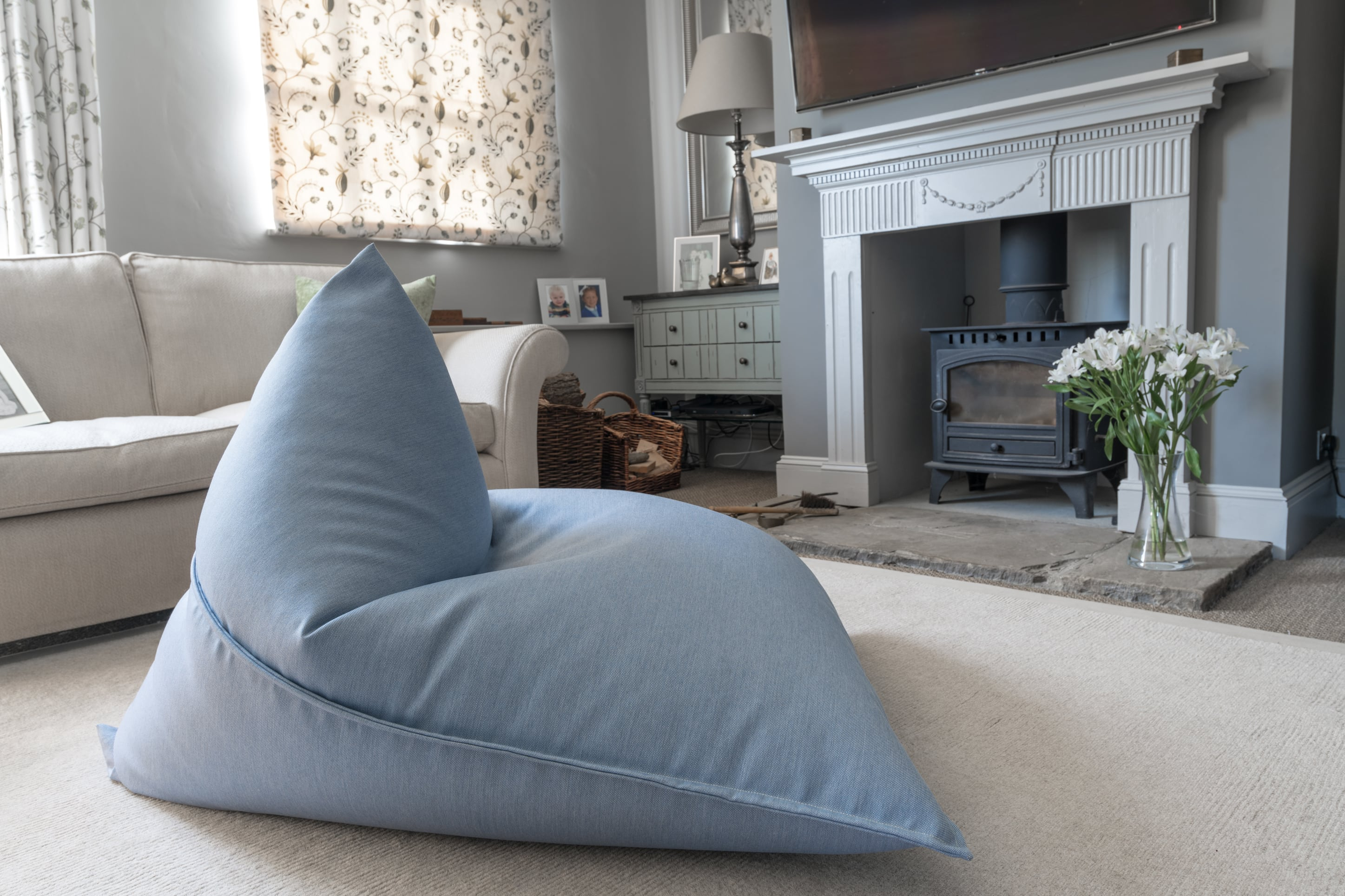 Armadillo Sun bean bag chair in ice blue fabric inside by fireplace