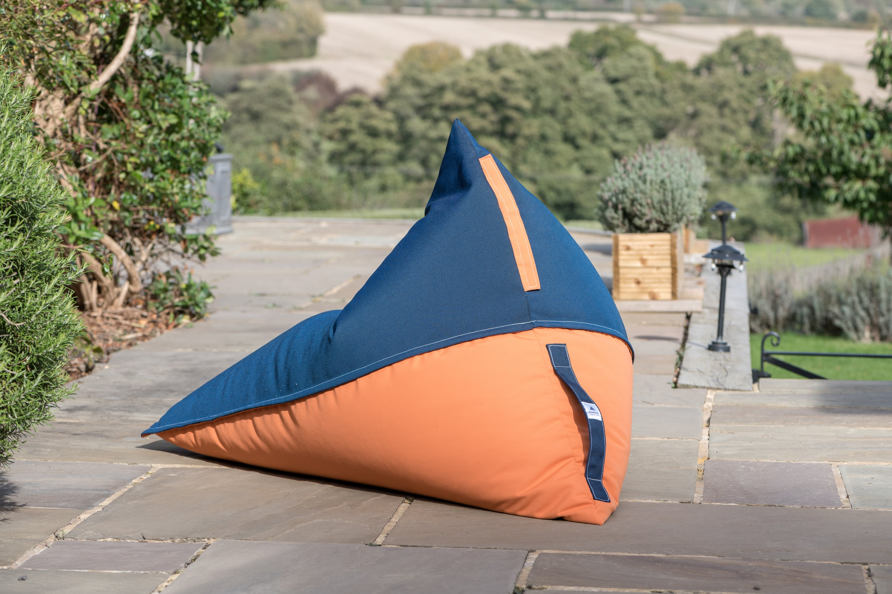 Armadillo Sun bean bag chair in orange and navy blue fabric outside