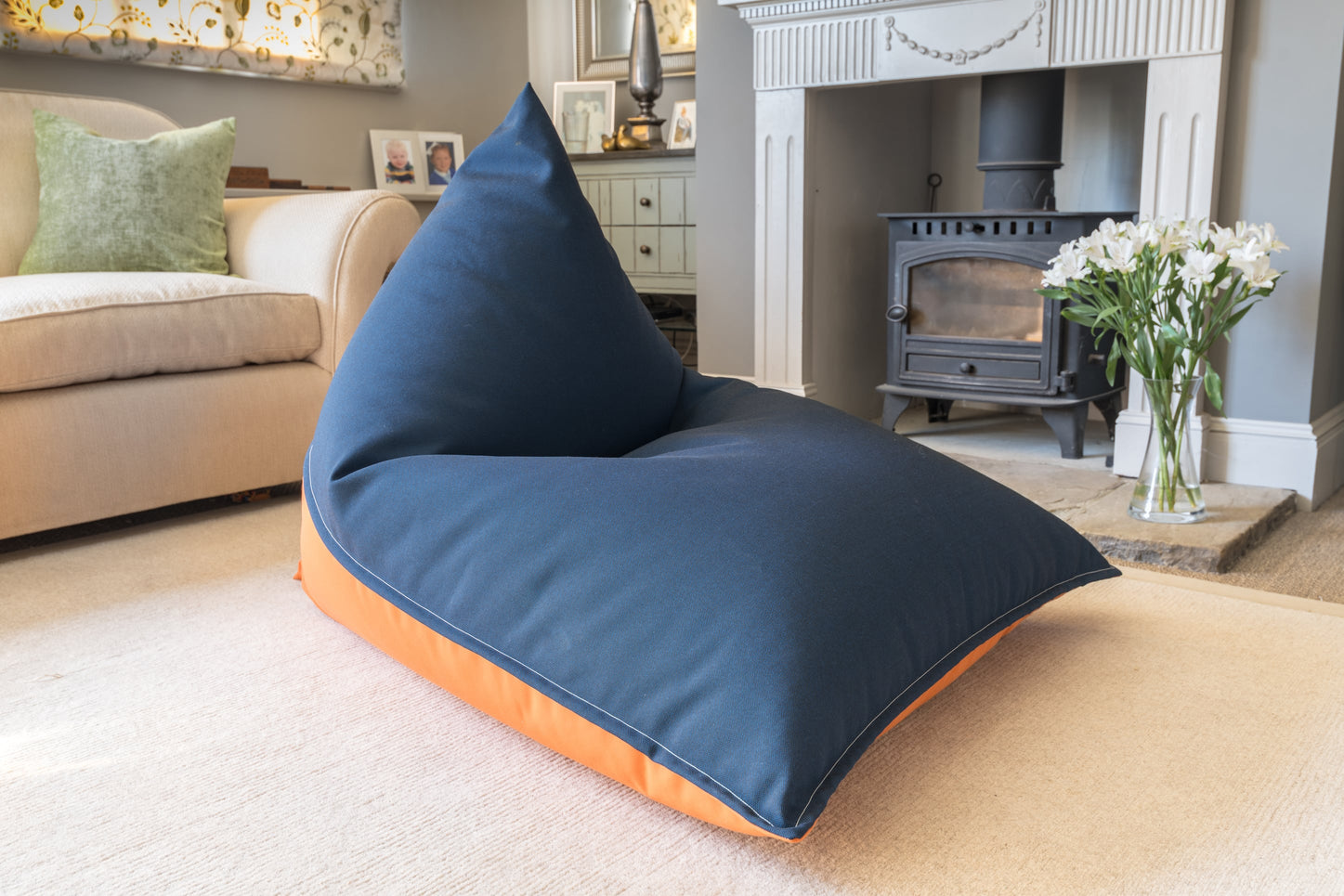 Armadillo Sun bean bag chair in orange and navy blue fabric indoors by fireplace