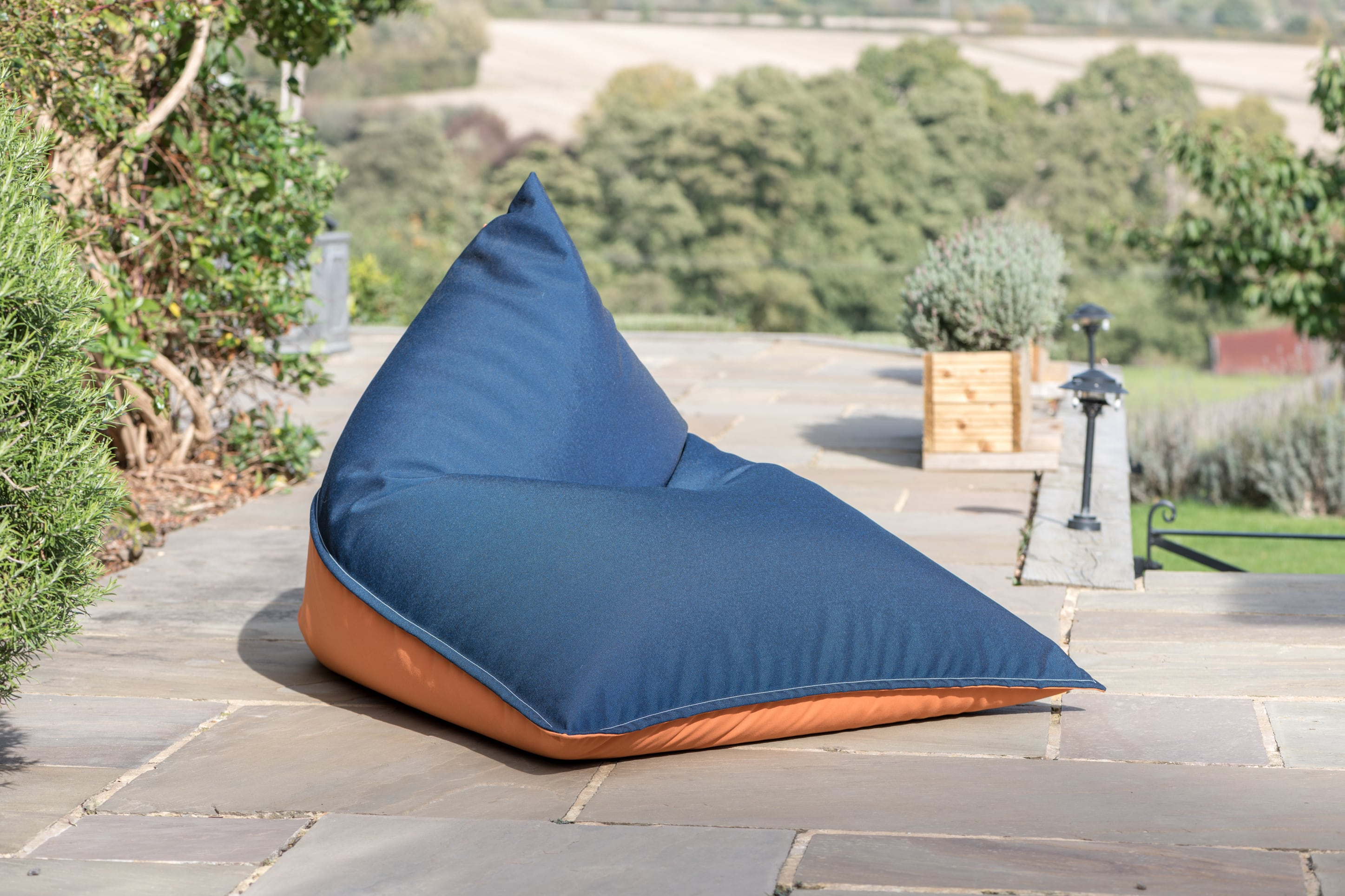 Armadillo Sun bean bag chair in orange and navy blue fabric outdoors