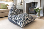 Armadillo Sun bean bag chair in navy blue and white palm pattern indoors