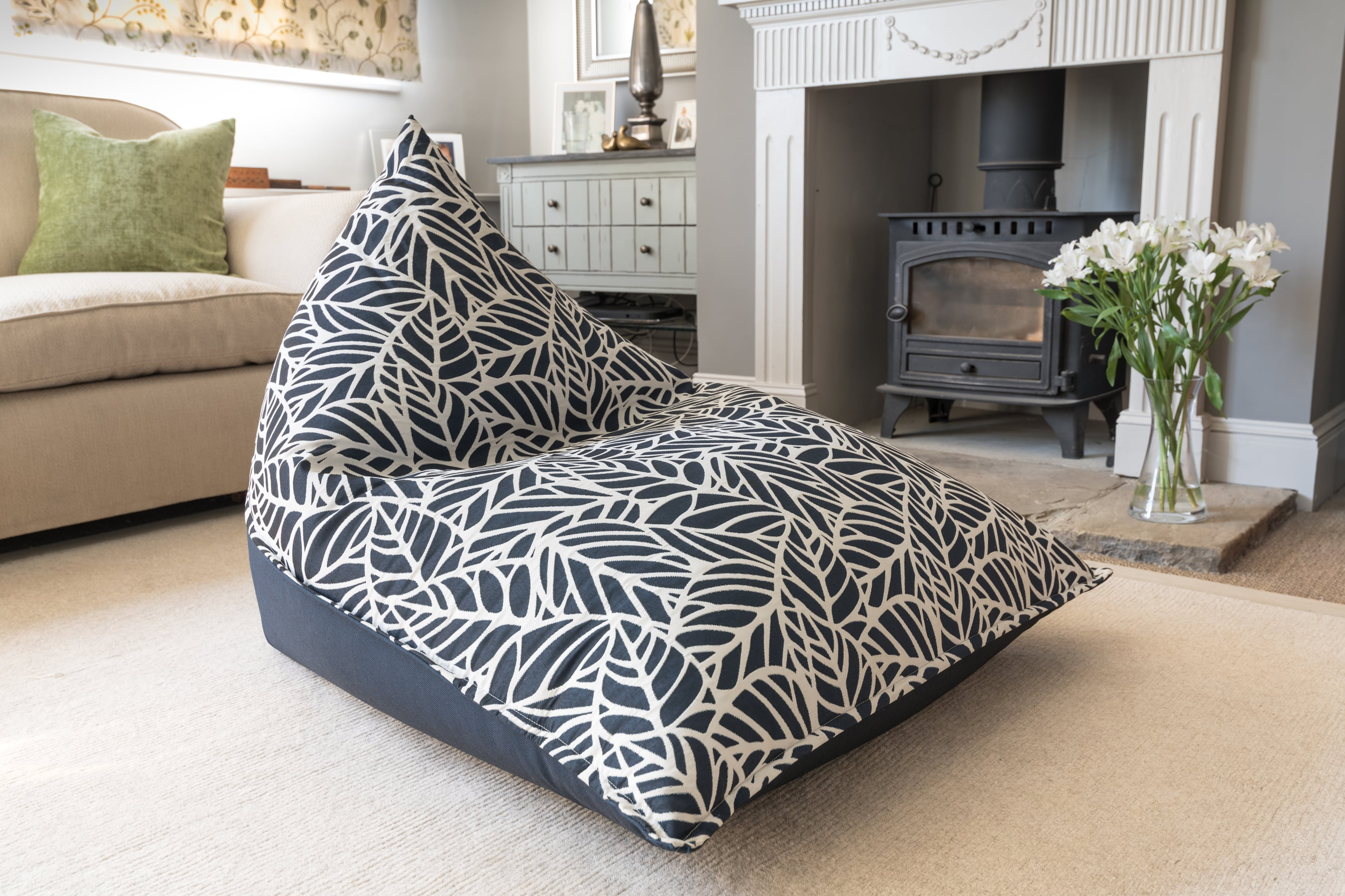 Armadillo Sun bean bag lounger in dark navy blue and white palm pattern indoors