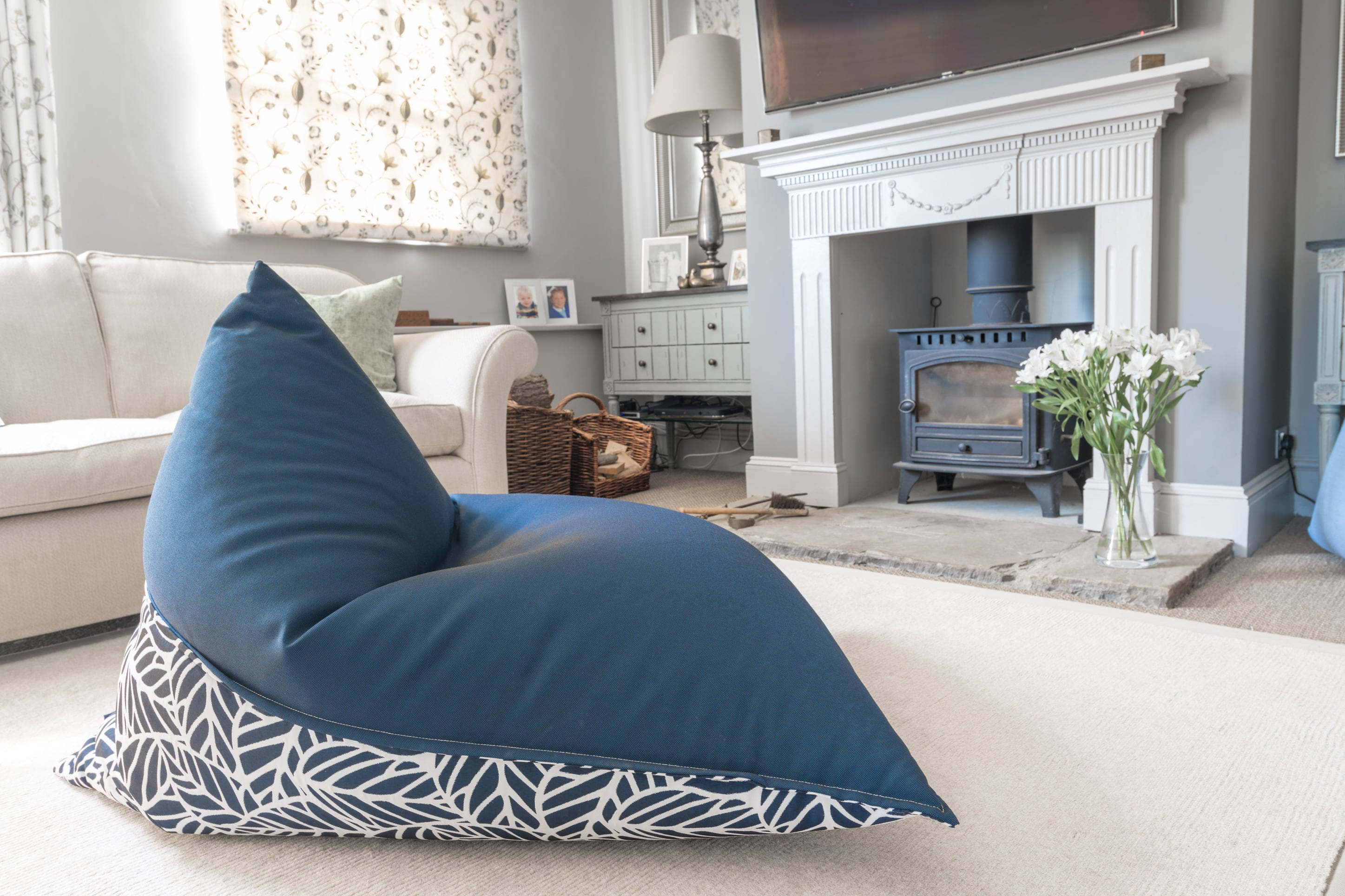 Armadillo Sun bean bag chair in navy blue and white palm pattern indoors by fireplace