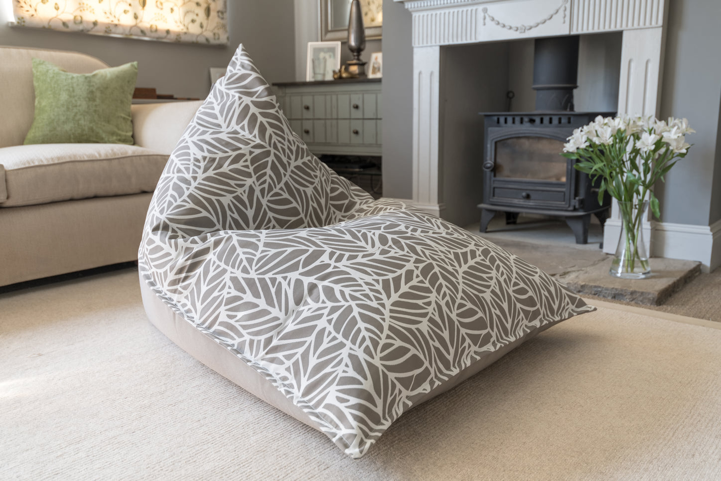 Armadillo Sun bean bag chair in neutral pumice and white palm pattern indoors by fireplace