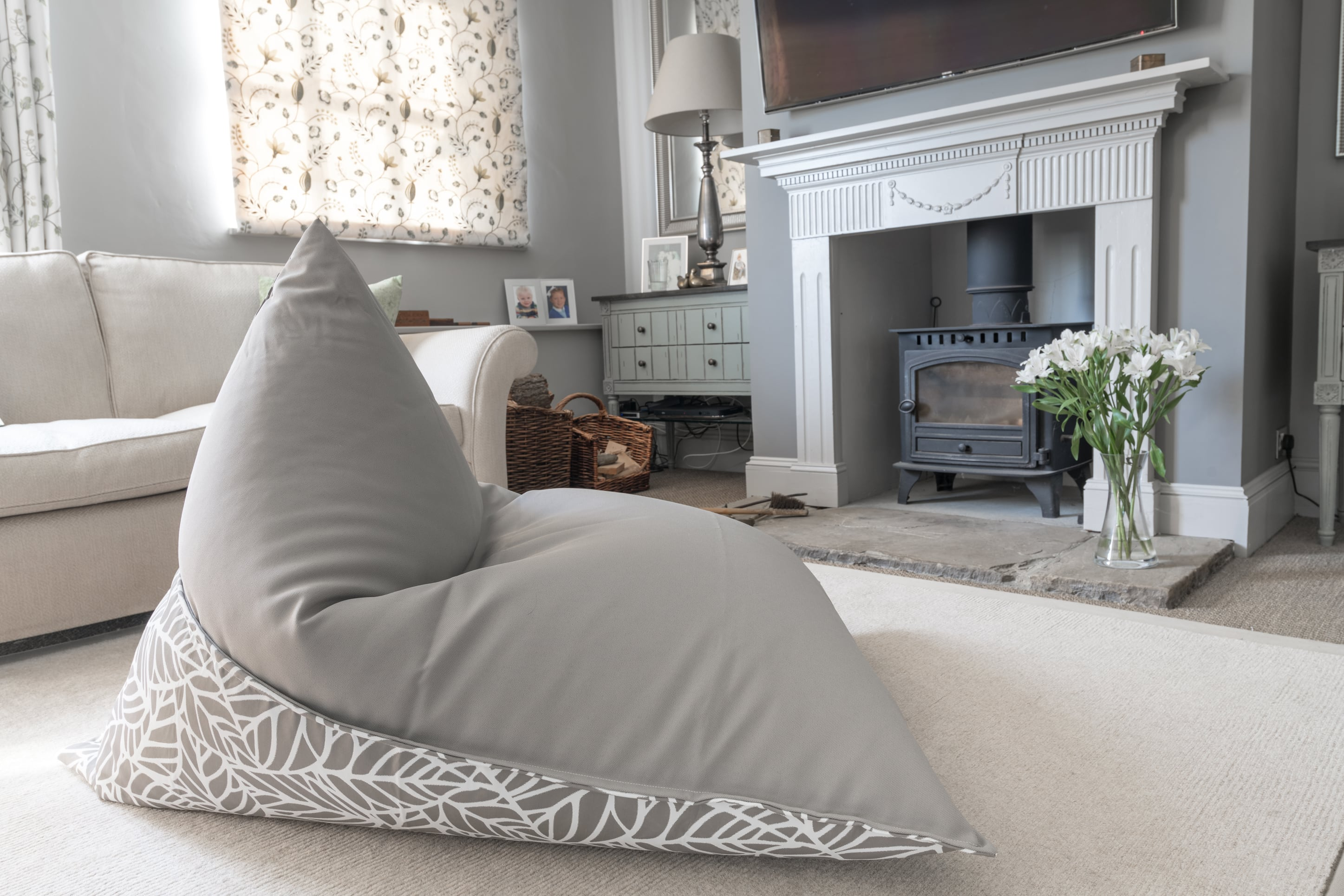 Armadillo Sun bean bag lounger in neutral pumice and white palm pattern indoors by fireplace